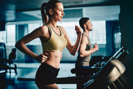 Photo pour Active female running on treadmill in gym with young man on background - image libre de droit