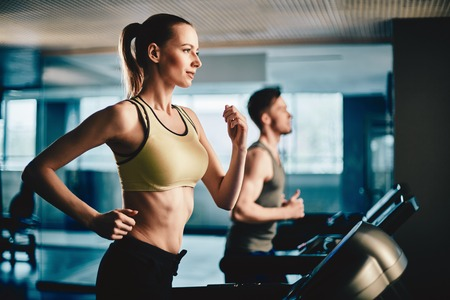 Photo for Pretty woman running on treadmill with fit young man on background - Royalty Free Image