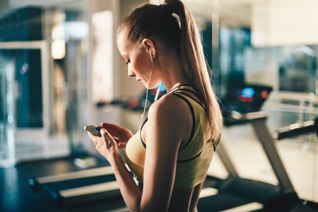 Photo pour Active girl with smartphone listening to music in gym - image libre de droit