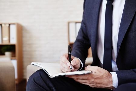Foto de Male employee with pen and notepad writing plan - Imagen libre de derechos
