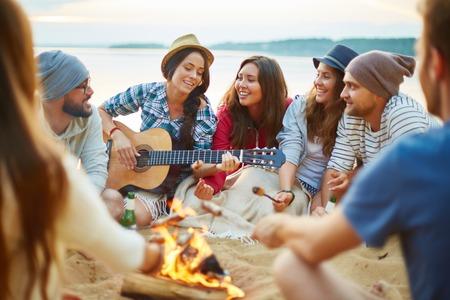 Foto de Friendly girls and guys singing by guitar by campfire - Imagen libre de derechos