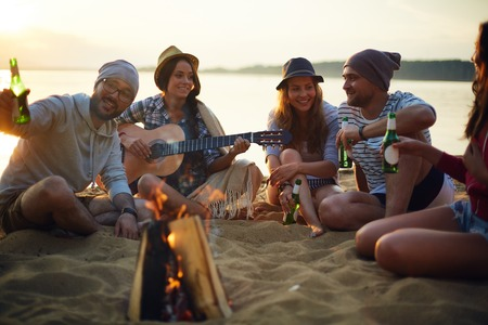 Photo for Happy friends with drinks and guitar sitting by campfire - Royalty Free Image