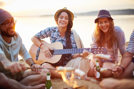 Photo for Friendly girls with guitar and drink singing on sandy beach by campfire among friends - Royalty Free Image