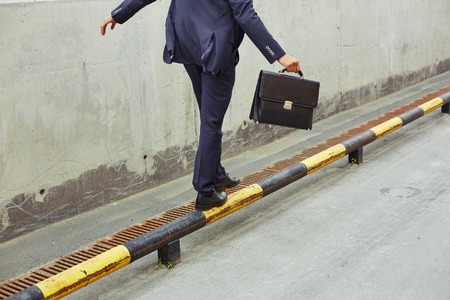 Photo pour Rear view of businessman with briefcase balancing on yellow-and-black road curb - image libre de droit