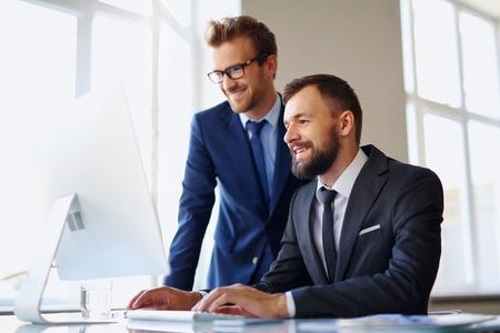 Foto de Two successful businessmen using computer at meeting - Imagen libre de derechos
