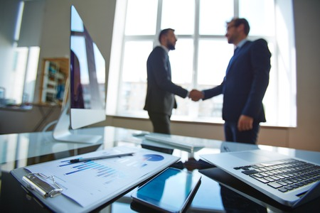 Photo pour Business objects at workplace with businessmen handshaking on background - image libre de droit