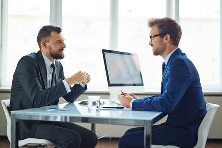 Photo pour Confident businessmen sitting by table during consultation - image libre de droit
