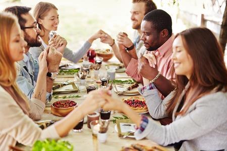 Foto de Group of young friends praying at Thanksgiving table - Imagen libre de derechos