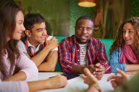 Foto de Friendly teens talking in cafe - Imagen libre de derechos