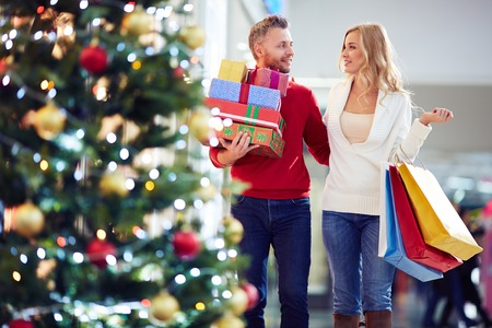 Photo pour Affectionate couple carrying Christmas presents while shopping in the mall - image libre de droit