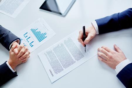Foto de Businessman signing contract after making agreement - Imagen libre de derechos