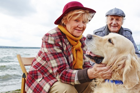 Photo pour Retired woman cuddling cute pet with her husband on background - image libre de droit