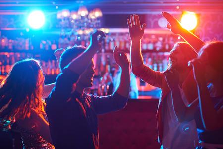 Photo pour Happy friends dancing at party in bar - image libre de droit