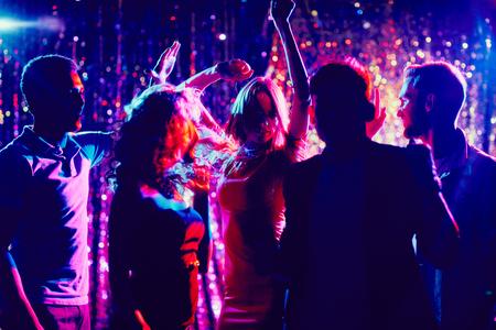 Foto de Group of guys and girls dancing in the night club - Imagen libre de derechos