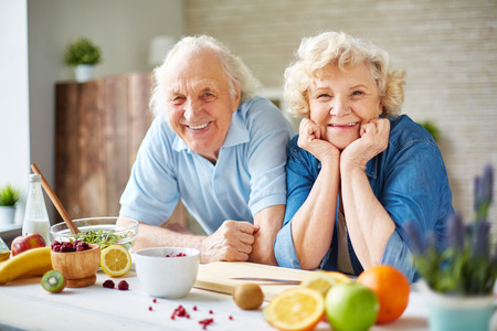 Photo pour Happy senior man and woman looking at camera in the kitchen - image libre de droit