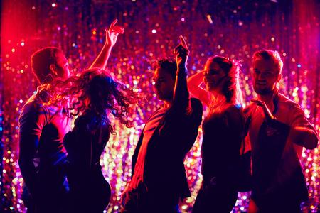 Photo pour Dynamic young friends dancing at disco party - image libre de droit