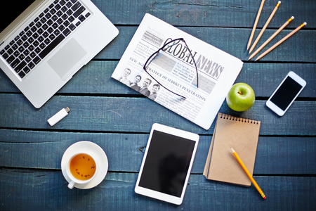 Foto de Technological devices, cup of tea, green apple, newspaper, eyeglasses and notebook with pencil on workplace - Imagen libre de derechos