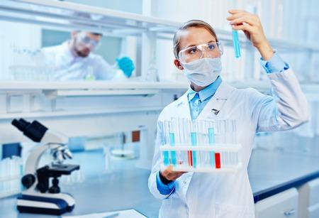 Foto de Young chemist analyzing liquids in lab on background of colleague - Imagen libre de derechos
