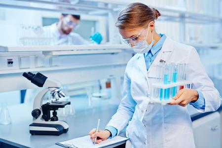 Foto de Young woman with flasks making notes in laboratory - Imagen libre de derechos