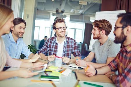 Foto de Group of colleagues discussing new project at meeting - Imagen libre de derechos