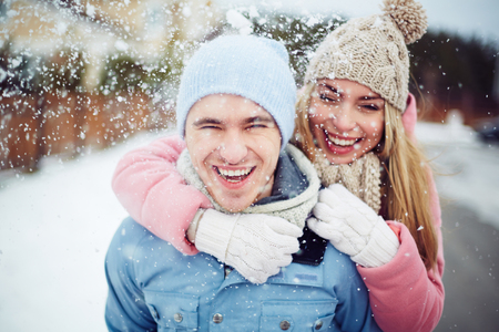 Photo for Young guy and girl in winterwear enjoying snowfall - Royalty Free Image