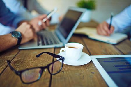 Foto de Cup of coffee and eyeglasses in working environment - Imagen libre de derechos