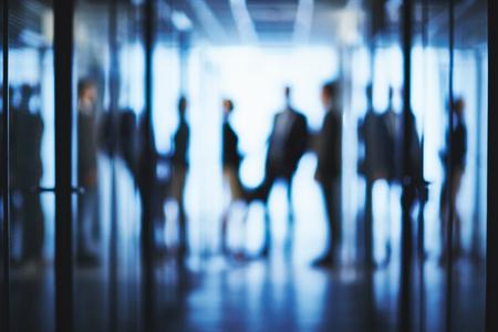 Foto de Blurred silhouettes of business people interacting in aisle of office center - Imagen libre de derechos