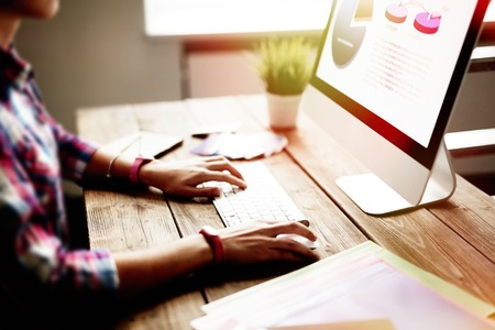 Foto de Young woman sitting in front of computer screen - Imagen libre de derechos