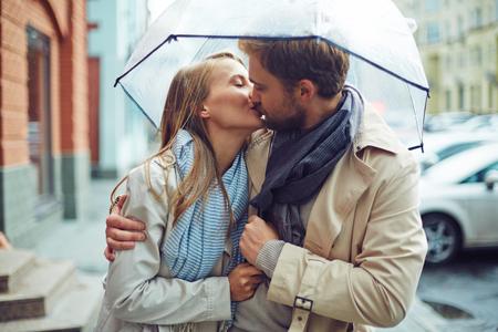 Photo pour Loving young couple in love under umbrella in the rain - image libre de droit