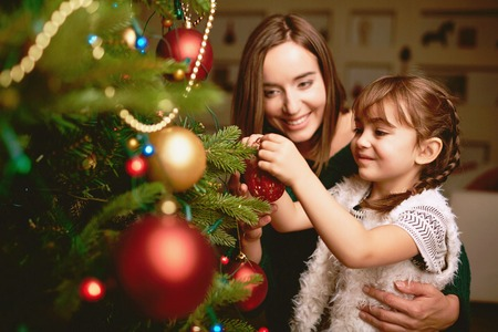 Foto de Cute girl and her mother decorating firtree on Christmas eve - Imagen libre de derechos