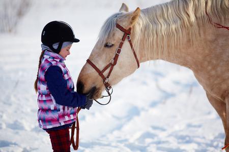 Photo pour Little girl with horse outdoor in winter - image libre de droit