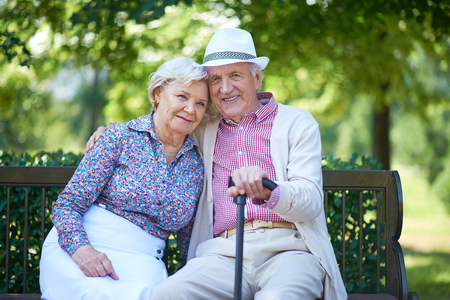 Foto de Romantic senior couple relaxed on the park bench - Imagen libre de derechos