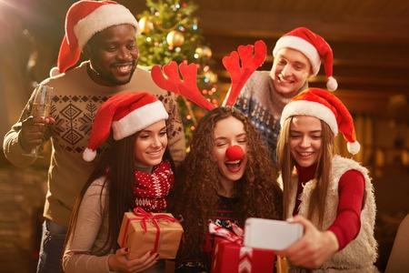 Photo for Joyful friends making selfie on Christmas evening - Royalty Free Image