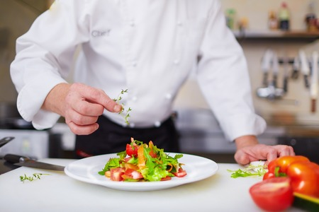 Photo for Male chef garnishing dish at the kitchen - Royalty Free Image