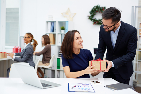 Foto de Young businessman giving his colleague Christmas present in office - Imagen libre de derechos