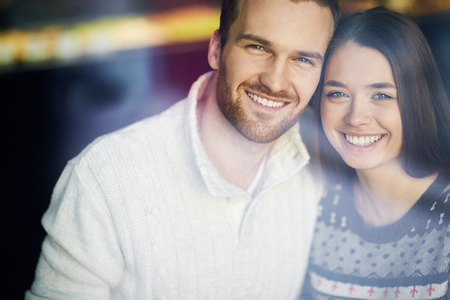 Affectionate couple looking at camera with smiles