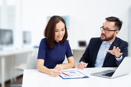 Foto de Two employees discussing document at meeting - Imagen libre de derechos