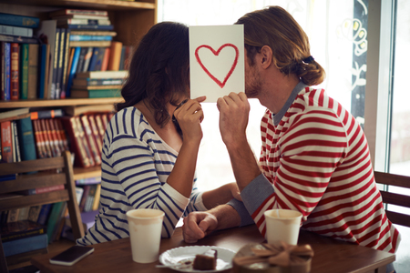 Photo for Young couple hiding behind the paper with red heart - Royalty Free Image