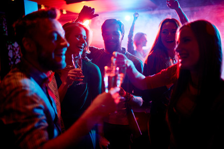 Photo pour Group of young people celebrating with drinks in nightclub - image libre de droit