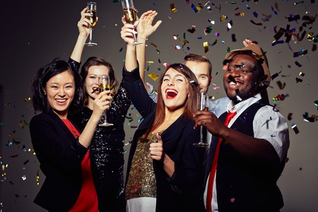 Joyful people toasting with champagne at party