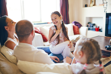 Photo for Cute girl sitting with her family and laughing at home - Royalty Free Image