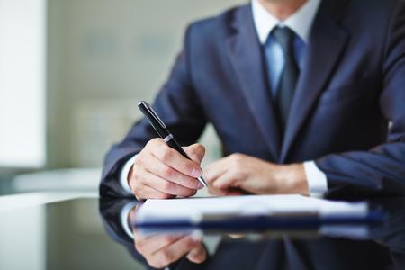 Photo pour Businessman sitting at office desk and signing a contract - image libre de droit