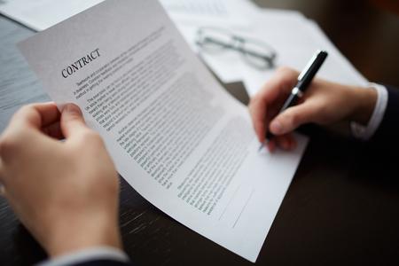 Foto de Close-up of male hands signing a contract with pen - Imagen libre de derechos