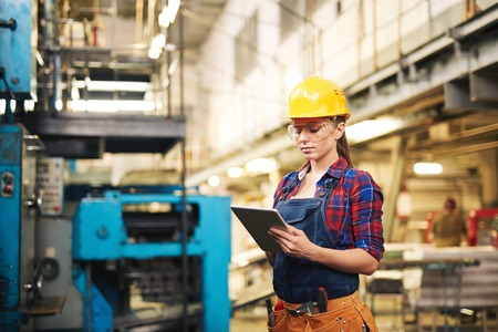 Photo pour Woman in protective clothing using touchpad in factory - image libre de droit