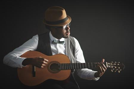 Photo pour Elegant young man in smart clothes and hat playing guitar - image libre de droit