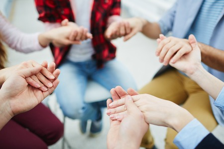 Foto de Circle of groupmates holding by hands at psychological session - Imagen libre de derechos