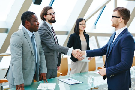 Two happy business partners handshaking after making agreement