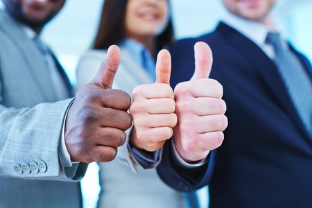 Photo pour Thumb up gesture shown by three business partners - image libre de droit