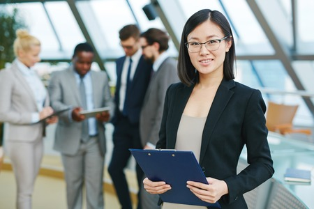 Pretty Asian businesswoman looking at camera in working environment