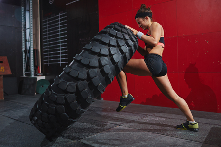 Photo for Active woman in sportswear flipping tyre in gym - Royalty Free Image